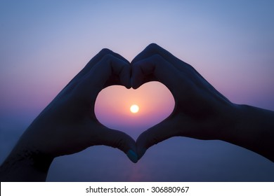 Two hands make a heart around the setting sun on a greek island holiday