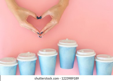 Two hands making heart between many paper cups of coffee . Coffee, love concept.
