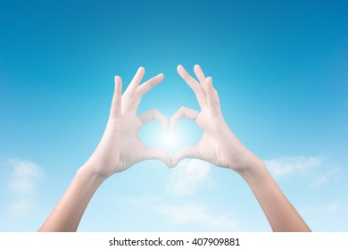 two hands making a heart shape in the blue sky
