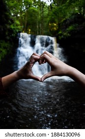 Two hands making a loveheart infront of a waterfall