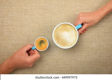 Two hands, man and woman, holding small espresso and big latte cappuccino coffee cups together over linen canvas background