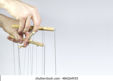 Two hands managing the threads of a puppet