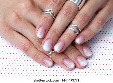 Two hands with manicure at the creative polka dot background. Ombre gradient nail design.