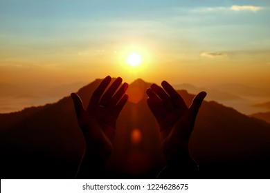 two hands of muslim who praying for hope and successful in sunrise. Use for Al-quran Quote background