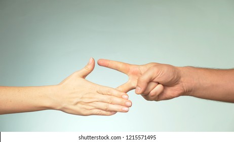 two hands on a blue background. Young man and woman are playing rock paper scissors