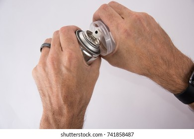 Two hands opening the lid of a spray paint can