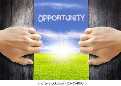 Two hands opening old wooden door to the new world. Opportunity concept.