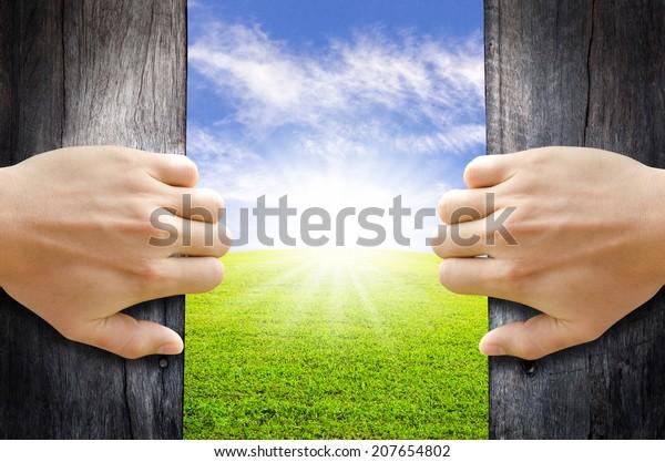 Zwei Hände öffnen alte Holztür zur neuen Welt. Neues Lebenskonzept.