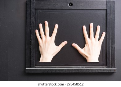 Two hands palm down with fingers spread against black covered wooden window hatch on black wall