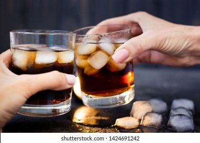 Two hands at a party holding glasses of whiskey with cola and ice touching them
