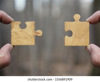 two hands person trying to connect couple Jigsaw wooden puzzle piece with tree  background. one part of whole. symbol of association and connection. success and business solution strategy.