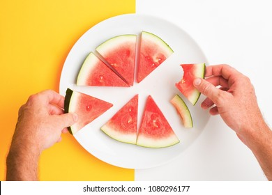 Two hands picking up sliced watermelon off a plate. Point of view of person eating.