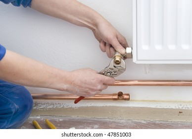two hands of plumber with pliers and radiator