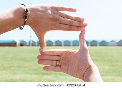 Two hands posing in front of the beach huts