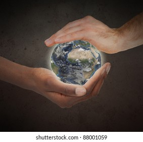 Two hands protecting a glowing planet globe against a white background