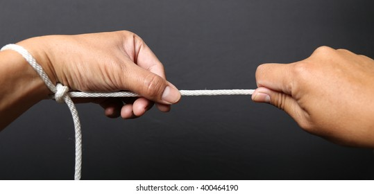 Two hands pulling a rope in opposite directions, isolated on black background