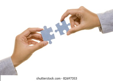 Two hands with two puzzles. Isolated over white background