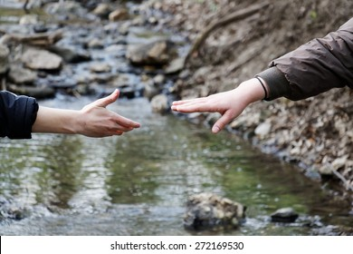 Two hands reaching touch each other