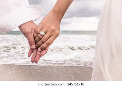 Two hands with ring on the beach