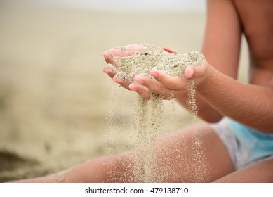 Two hands in a sand on the beach. Boy playing in the sand on the beach. Close up