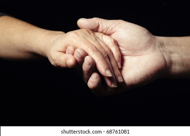 Two hands of senior people holding each other on a black background