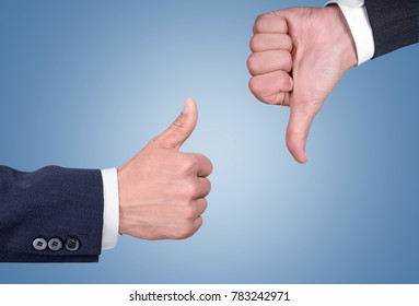 Two hands showing different gestures. Thumb up and thumb down