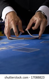 Two hands shuffling a deck of cards in a casino