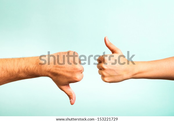 Two hands signalling thumbs up and thumbs down. The smooth hand on the left is making a thumbs up gesture while the hairy hand on the right is making a thumbs down gesture.