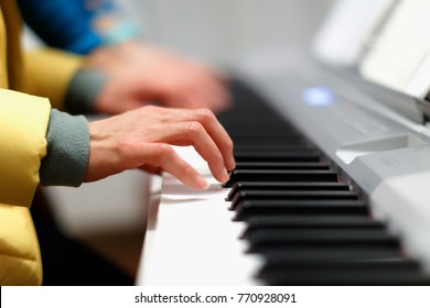Two hands together on a electronic piano keyboard