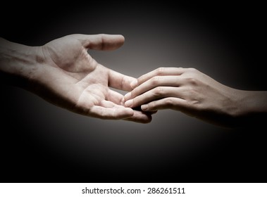 two hands are touching each other over black background, concept of solidarity or empathy.