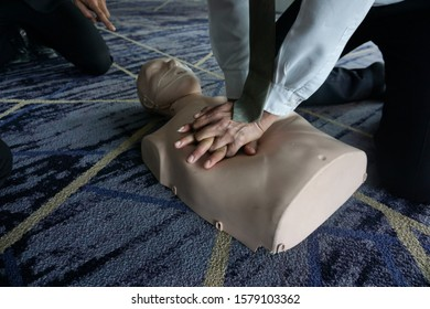 Two hands of trainee pressing on chest of mannequin for CPR first aid  of basic life support training , instructor sitting in background.