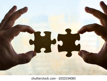 two hands trying to connect couple puzzle piece on house background. Jigsaw  wooden puzzle against home with windows.  part of whole. symbol of association and connection. business strategy.