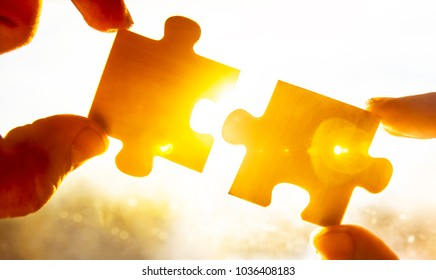 two hands trying to connect couple puzzle piece with sunset background.  copy space for inscription or objects. Jigsaw alone wooden puzzle against sun rays. one part of whole. symbol of association