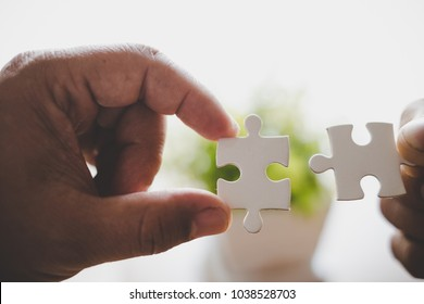 two hands trying to connect couple puzzle piece. one part of whole. symbol of association and connection. business strategy