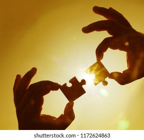 two hands trying to connect couple puzzle piece with sunset background. Jigsaw against sun rays. one part of whole. symbol of association and connection. business strategy