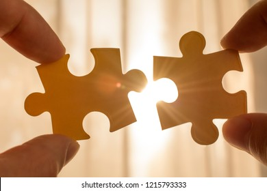 two hands trying to connect couple puzzle piece. with sunset background. symbol of association and connection, business strategy, completing, team support and help concept