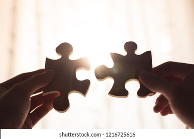 Two hands trying to connect couple wooden puzzle piece. Concept of association and connection, business strategy.