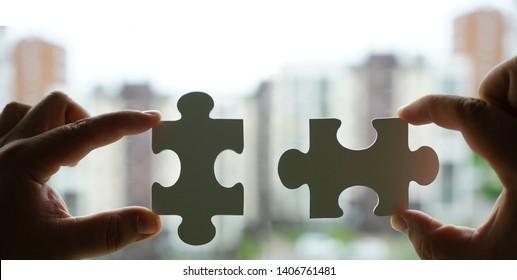 zwei Hände, die versuchen, ein paar Puzzleteil auf Haushintergrund zu verbinden. Puzzle aus Holz mit Fenster.  Teil des Ganzen. Vereinigungs- und Verbindungssymbol. Geschäftsstrategie