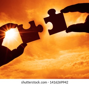 two hands trying to connect couple puzzle piece with sunset background. Jigsaw alone wooden puzzle against sun rays. one part of whole. symbol