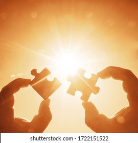 two hands trying to connect couple puzzle piece with sunset background. Jigsaw alone wooden puzzle against golden sun rays. one part of whole. symbol of association and connection. business strategy.