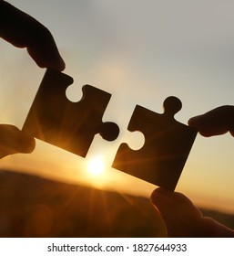 two hands trying to connect couple puzzle piece with sunset background. Jigsaw alone wooden puzzle against sun rays. one part of whole. symbol of association and connection. business strategy