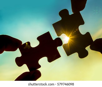 two hands trying to connect couple puzzle piece with sunset background. Jigsaw alone wooden puzzle against sun rays. one part of whole. symbol of association and connection. business strategy.