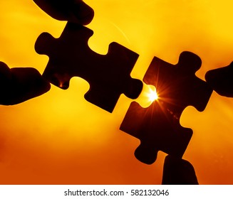 two hands trying to connect couple puzzle piece with yellow sunset background. Jigsaw alone wooden puzzle against sun rays. one part of whole. symbol of association and connection. business strategy.