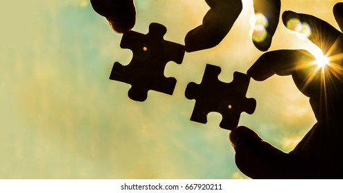 two hands trying to connect couple puzzle piece with sunset background. empty copy space. Jigsaw wooden puzzle against sun. one part of whole. symbol of association and connection. business strategy.