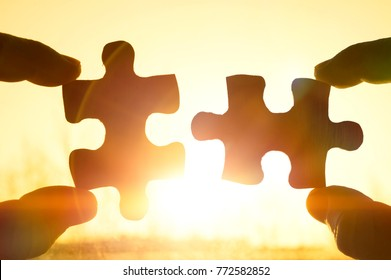 two hands trying to connect couple puzzle piece with sunset background. Jigsaw alone wooden puzzle against sun rays. Close-up. Teamwork, partnership, business, cooperation and management concept.