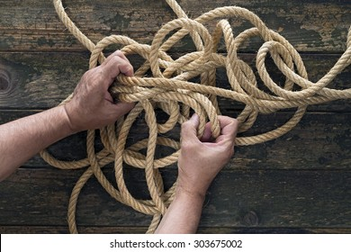 Two hands trying to untangle a rope. Wooden background