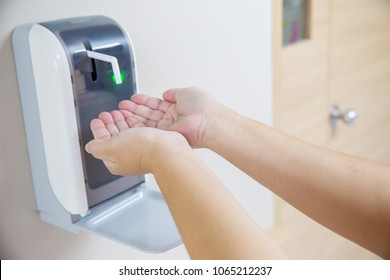 Two Hands under the automatic alcohol dispenser. Infection and hospitably concept. save and protect disease virus against germs and clean in the public area.