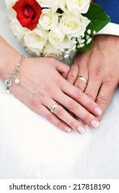 two hands with wedding rings and flowers