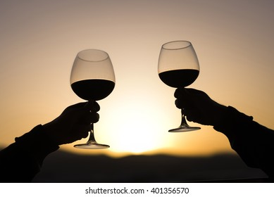 Two Hands and wineglass silhouette on sunset.