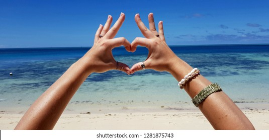 Two hands of a woman forming a heart in front of a white sand beach and the ocean with crystal-clear, blue waters on Mana Island, Fiji